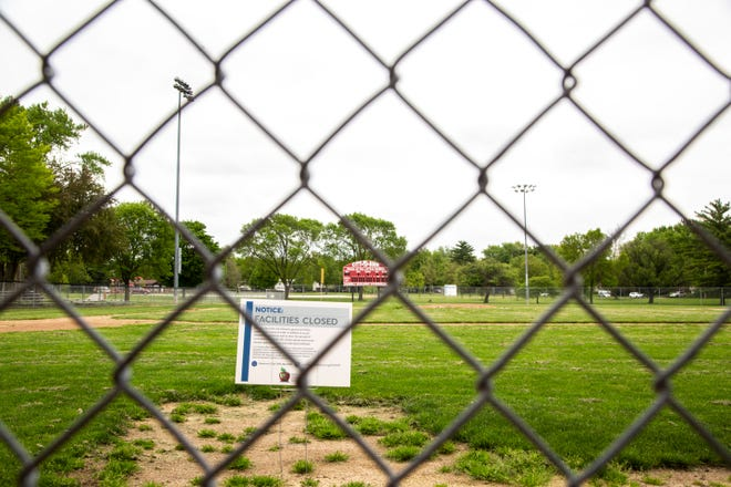 "A sign from the Iowa City Community School District reading ""Facilities Closed"" is seen at the baseball field for Iowa City High during the novel coronavirus, COVID-19, pandemic, Wednesday, May 20, 2020, at Mercer Park in Iowa City, Iowa."