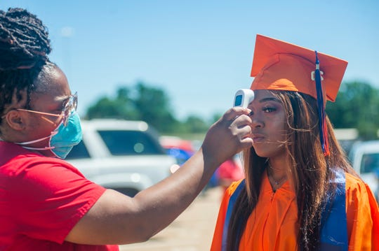 Callaway High School graduate Keyarie Harris, of Jackson, Miss., pauses to get her temperature taken by Mallory Jones, RN, with Jackson Public Schools, in Jackson, Miss., before heading into Mississippi Veterans Memorial Stadium in Jackson, Miss., for her graduation ceremony Wednesday, May 20, 2020. The JPS school graduations are being staggered, using face masks and adhering to social distancing. The ceremonies are being recorded for a virtual graduation to be played back at a later scheduled time.