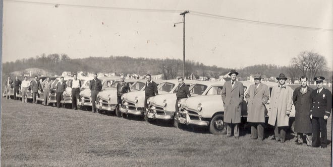 Photo of the 2300 Cab Company's cars taken in 1949 at the fairgrounds for an ad to promote their new service--Radio Controlled Cars! Drivers are pictured to the left, then Ray Smith, co-owner; Dave Grove, Safety Director; Mayor Fred Von Stein; Buddy Snyder, co-owner; and Police Chief Hutsler.