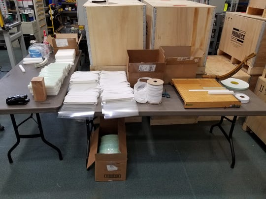 Supplies for making Personal Protection Equipment to fight against COVID-19 include strips of elastic and pieces of foam, seen set up for assembly at Brighton manufacturer Promess.