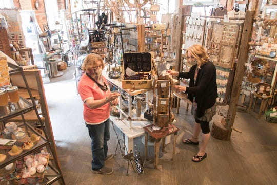 Jewelry maker Joyce Greene of Howell, left, brings some of her one-of-a-kind jewelry to Finding Roots, as store co-owner Tirzah Sirken adjusts a display Thursday, May 21, 2020.