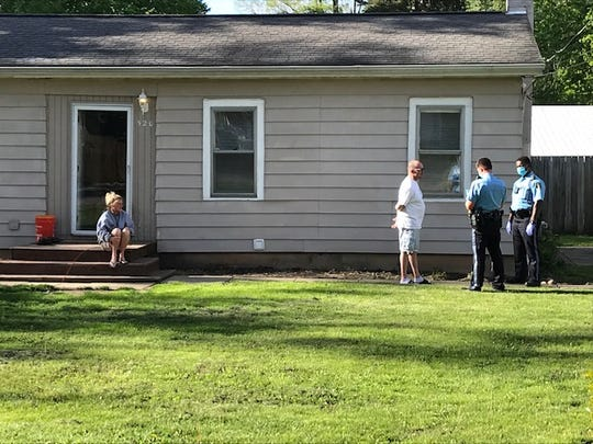 Officers speak with residents of a north Lansing neighborhood after a reported shooting on Thursday, May 21, 2020.