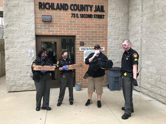 From left, Lt. Katina Douglas,  Sgt. Kristin Gillis, Danny Haubiel of Gionino's Pizzeria, and Sgt. Chris Plantz stand outside the Richland County Jail. Haubiel delivered pizzas to the jail staff Thursday, donated by pizzeria owners Roger and Kristina Nelson.