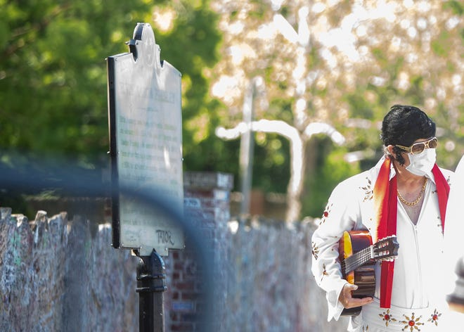 A man dresses as Elvis Presley wearing a face mask stands outside the mansion at Graceland in Memphis, Tenn., on Thursday, May 21, 2020. Graceland reopens for the first time since closing March 20 amid the coronavirus pandemic.
