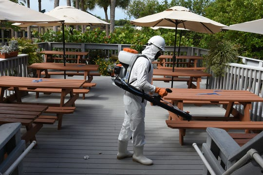 Technician Owen Maynard disinfects the seating area at the Tigertail Beach Cafe. HydroClean Environmental Solutions is a startup dedicated to disinfecting local businesses to enhance customer safety.