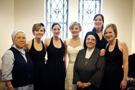 Sr. Gabriella Nguyen, left and Sr. Monica Fumo pose with bride Chiarra Millikan and her sisters and bridesmaids at her wedding.