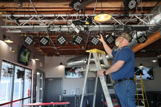 Paul Budiac, owner of Paulie's Pub and Eatery in West Allis, gets the pub ready to host concerts over the weekend after the long shutdown. Here Budiac tightens up some light fixtures mounted on a rack and pointed at the stage.