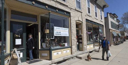 A pedestrian passes Up the Creek while owner Debbie Lauer is in the doorway in downtown Cedarburg, Wisconsin. The home decor and and gift store just reopened after the coronavirus shutdown.