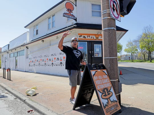 Bryant Wilcox, Battlebox Studios co-owner, waves to a motorist after blowing their horn while he puts out a sign after reopening the family-owned gaming store at 5431 W. Lisbon Ave. in Milwaukee on May 12.