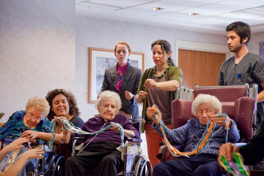 """Participants in the Penelope Project at Luther Manor senior living community show an art piece they wove for the performance of """"Finding Penelope."""""""