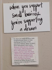 A  card encouraging people to patronize small businesses is shown at Up the Creek.