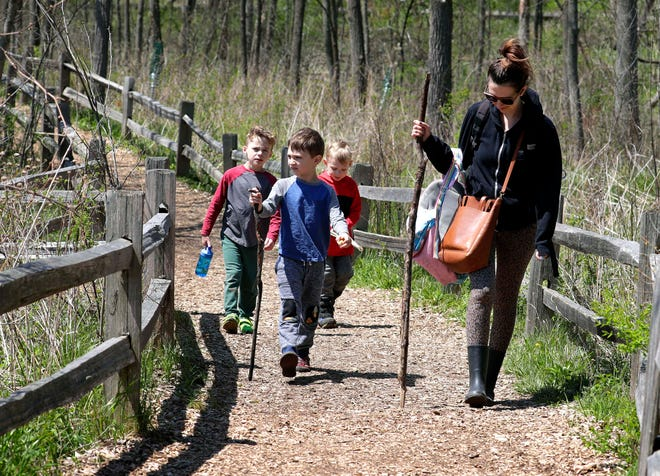 Melissa Steinseifer and her children, from left, Milo,7; Max,6; and Modi, 4, enjoy the sights and sounds along the nature trail in the Wehr Nature Center at Whitnall Park. Milwaukee County Parks are open with limited venues as residents social distance while enjoying the nature trails, blooming tulips and other warm sunny Spring weather.