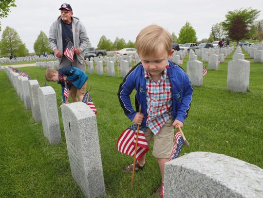 Jayden McHenry, right, 4, of Mukwonago places a flag Thursday at Southern Wisconsin Veterans Memorial Cemetery in Union Grove, along with his grandfather Wayne Barkley and brother Jack McHenry, 6, both of Mukwonago.
