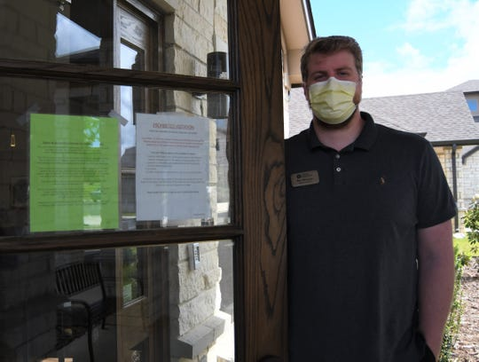 Ben Worlow, administrator for Hiram Shaddox Health and Rehab, stands next to a pair of signs on the facility's front door notifying visitors that they are not permitted inside at this time. The state's nursing homes and long-term care facilities were the first facilities to be closed to visitors amid the COVID-19 pandemic, and have not yet reopened to the public.