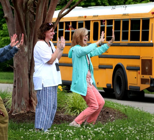 Jennifer Clunie, left and Amy Miller, right both with the Murfreesboro City Schools Central office wave at buses loaded with Mitchell Neilson Schools teachers and faculty during a bus parade held on Thursday, May 21, 2020, passed in front of the Central Office. The buses and cars in the parade passed by the Central office to honor Linda Gilbert, the Director of Murfreesboro City schools that died on Wednesday.
