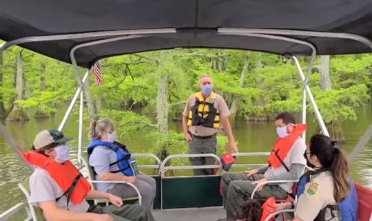 Visitors to Reelfoot Lake State Park wear masks on a pontoon tour.