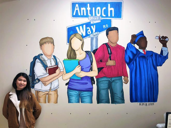 "Kim Boih stands next to a mural she painted at Antioch High School. People often ask why she didn't include faces on the students she painted. She did it purposefully, so that anyone who saw the mural could feel like they fit in the images, so they could say, ""Maybe this could be me."""
