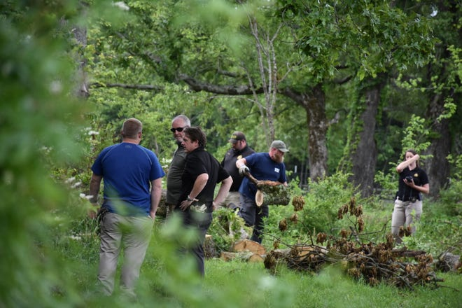 The 23rd Judicial District Attorney Ray Crouch, left, black shirt, talks with officials as digging and searching continues in the Daniels' family backyard on May 21, 2020. It was at the home in 2018 that Joe Clyde Daniels was first announced missing. Later, his parents were charged in the disappearance -- his father Joseph Daniels is charged with murder.