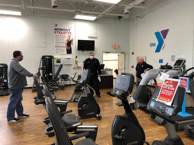 Chad Brown, Licking County Health Department, reviews safety precautions in place at Licking County Family YMCA branch in Newark with YMCA leaders Ed Bohren and Alan Cecutti prior to the May 26th reopening of fitness facilities.