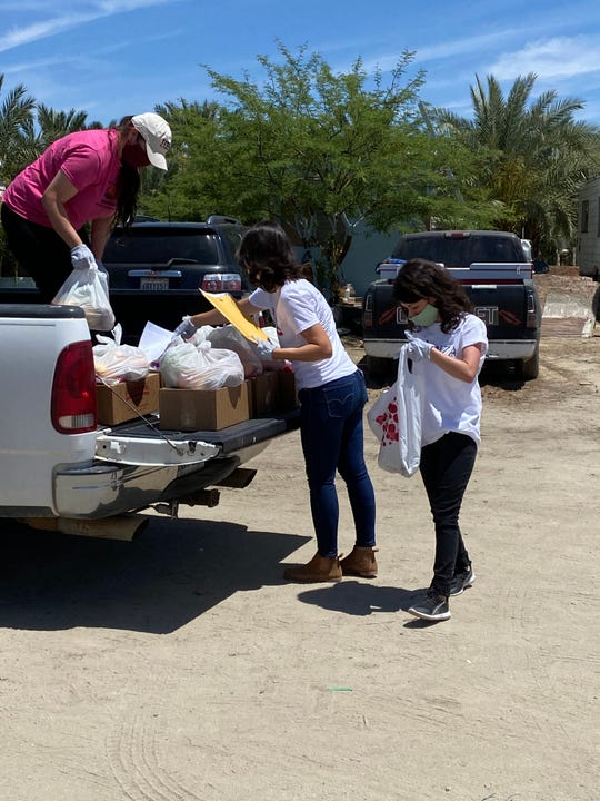 Mariana Roman with Coachella Vally Parents; Silvia Paz, executive director with Alianza Coachella Valley, and Patricia Carrillo, project manager with Alianza Coachella Valley, distribute food in the rural Eastern Coachella Valley.