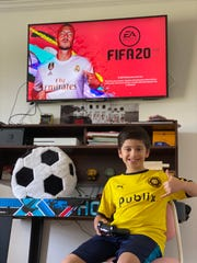 Perdido Bay FC soccer player Benjamin De Melo smiles while playing FIFA 20 during the COVID-19 pandemic.