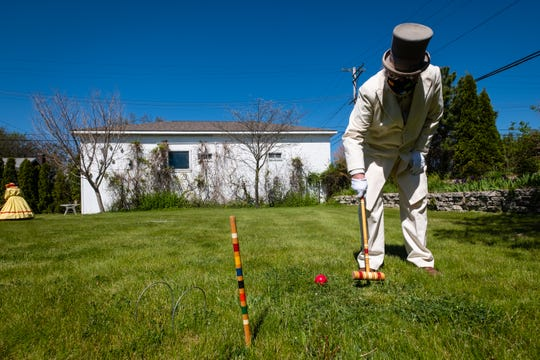 Dressed in 19th Century summer clothing, Brian Wandelt hits a croquet ball Thursday, May 21, 2020, in Port Huron. To help get them out of the house, a group of Civil War enthusiasts decided to dress the part and play a game of croquet.