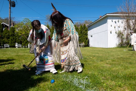 Dressed in clothing similar to what was worn by 19th Century Odawa Indians, Joan Tipkey Jacobs, right, helps her great niece Eryn Breeze, 12, with her croquet swing Thursday, May 21, 2020, in Port Huron. To help get them out of the house, a group of Civil War enthusiasts decided to dress the part and play a game of croquet.