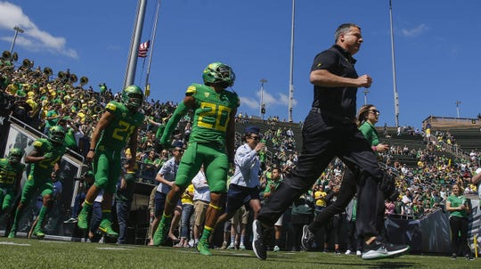 Oregon head coach Mario Cristobal leads the Thunder team onto the field at the Oregon Spring Game at Autzen Stadium on April 21, 2018, in Eugene, Ore.