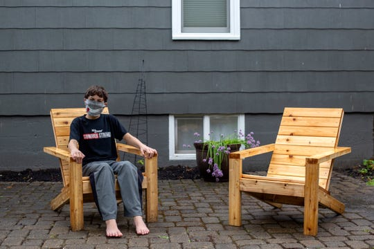 Will Schumacher sits on one of the Adirondack chairs his father, Jeff, built at their home in Salem on May 21, 2020.