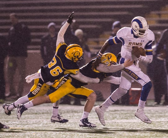 Angelo State's Kyle Washington runs through the tackle attempts of a couple of Texas A&M-Commerce defenders on Nov. 15, 2014, in the Rams' 35-33 win over Commerce for the Lone Star Conference Playoff Championship.