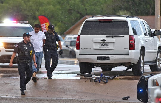 A suspect, far left, is arrested by San Angelo Police Department officers at the scene of a crash where a child, 7, on a bicycle was hit by a vehicle in the 1800 block of College Hills Boulevard. The suspect in the photo was not driving the vehicle which struck the child.