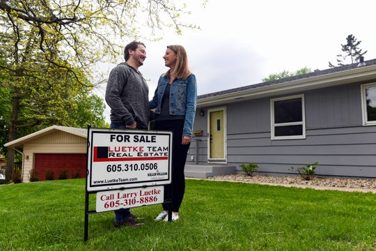 "Zak and Jenn Karn stand with the ""for sale"" sign on the lawn of their new home on Thursday, May 21, in Sioux Falls."