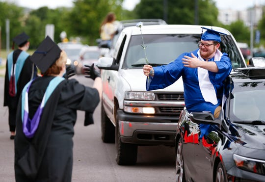 Austin Parker gives an air hug to his teachers during a drive through graduation ceremony for OTC Middle College students on Wednesday, May 20, 2020.