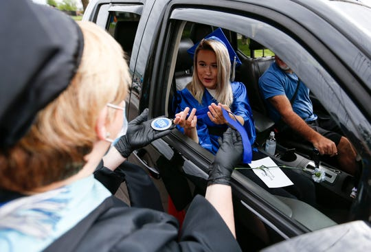 Madeline Alexander is handed a medal by Cindy Wilson, assistant director of OTC's Middle College, during a drive through graduation ceremony for OTC Middle College students on Wednesday, May 20, 2020.