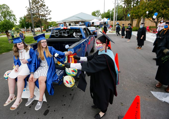 Sophie Talburt (left) and Sarah Peltz ride in the back of a pickup truck as Jo Fritts, a Middle College instructor, hands them flowers during a drive through graduation ceremony for OTC Middle College students on Wednesday, May 20, 2020.