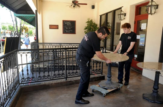 Leo Vazquez, left, general manager at Rabalais' Bistro in Santa Paula, and manager Garrett Newman rearrange tables on the restaurant's sheltered patio. It added limited dine-in service on June 4.
