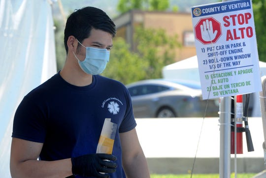 Leo Perez, a paramedic with Gold Coast Ambulance, helps at a drive-thru coronavirus testing site in Santa Paula, one of three offered by the County of Ventura.