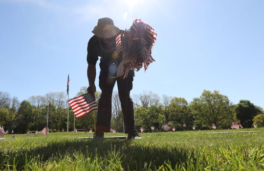 Facilities Management worker Lance Beal places American Flags at the grave markers of veterans at Fredrick Loescher Veterans Cemetery in Spring Valley on Thursday, May 21, 2020.  Approximately 5000 flags will be placed on the graves of veterans at two cemeteries in Rockland County.
