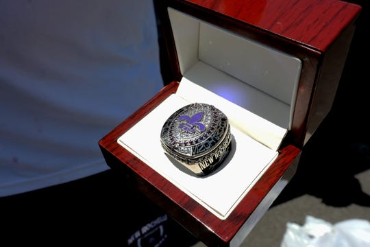 With coronavirus quarantine restrictions in place, the New Rochelle High School football team has not been able to gather to celebrate their state championship, so with a New Rochelle police and fire department escort, the team's coaches and supporters drove to each players' home May 21, 2020 to present them with their rings, one of which is displayed.