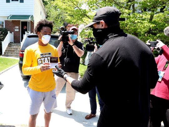 New Rochelle High School football assistant coach Rich Tassello presents a state championship ring to football player Ray Dixon, outside Dixon's home May 21, 2020. With coronavirus quarantine restrictions in place, the team has not been able to gather to celebrate their championship, so with a New Rochelle police and fire department escort, the team's coaches and supporters drove to each players' home Thursday to present them with their rings.