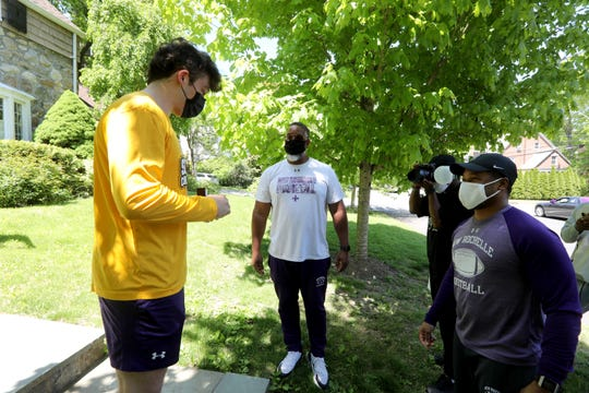 New Rochelle High School football assistant coach Greg Foster, left, and new head coach Ray Rhett, right, present a state championship ring to football co-captain Calvin Jackson outside Jackson's home May 21, 2020. With coronavirus quarantine restrictions in place, the team has not been able to gather to celebrate their championship, so with a New Rochelle police and fire department escort, the team's coaches and supporters drove to each players' home Thursday to present them with their rings.