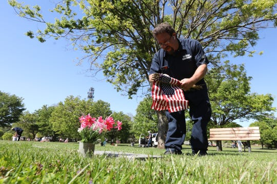 Facilities Management worker Jason Spong places American Flags at the grave markers of veterans at Fredrick Loescher Veterans Cemetery in Spring Valley on Thursday, May 21, 2020.  Approximately 5000 flags will be placed on the graves of veterans at two cemeteries in Rockland County.