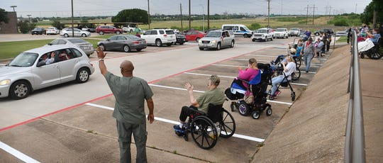 Families of residents at Midwestern Healthcare Center particpate in a parade Thursday morning.