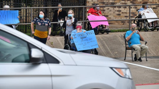 Residents and staff of Midwestern Healthcare Center wave and hold signs as theiir families drive by in a parade for them Thursday morning.