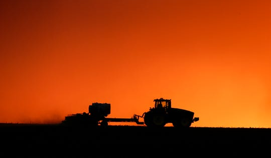A farmer is silhouetted by the setting sun as a field is planted near Walford, Iowa. U.S. farmers across the nation leaned more heavily upon the federal government last year to finance their agricultural operations amid low commodity prices and trade disputes, and more of the money they borrowed from taxpayers is now delinquent.