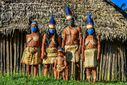 Colombian Huitoto indigenous people pose wearing face masks, amid concerns of the COVID-19 coronavirus, in Leticia, department of Amazonas, Colombia on May 20, 2020.