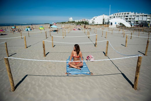 A woman sunbathes in a roped off distancing zone marked out by the municipality along the beaches in La Grande Motte, France, on May 21, 2020, as the nation eases lockdown measures taken to curb the spread of the COVID-19 pandemic, caused by the novel coronavirus.  The local municipality dubbed this set up 'organized beaches', the first in France to implement separated zones for beach goers in order to respect social distancing.