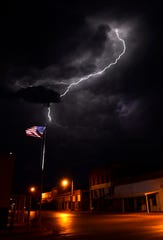 Lightning strikes Thursday in the background behind an American flag at Edwards and North First streets in Merkel.