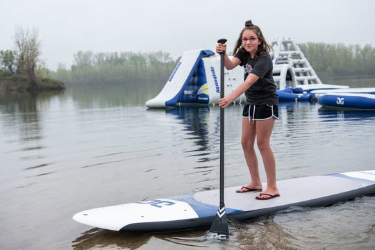 Rylee Berry, 11, paddle boards at her family's aquapark named The Aqua Pit on Friday, May 22, 2020 in Coldwater Township, Mich. The Berry family plans to open their new park this Saturday.