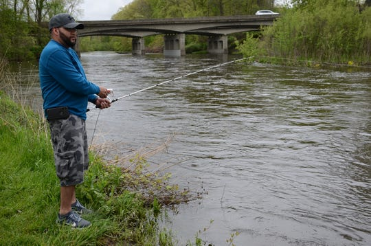Jose Lugo of Battle Creek was fishing Friday along the banks of the swollen Kalamazoo River at Historic Bridge Park in Emmett Township.  Trace Christenson/The Enquirer